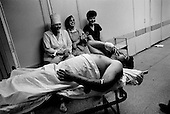 Moscow, Russia.Emergency ward.1994.A mafia hit takes a drag on a nurse?s cigarette on his way into surgery.