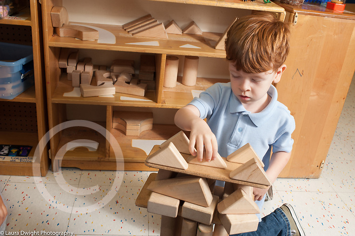 Education preschool 3-4 year olds boy placing triangle blocks balanced on board on top of wooden block construction