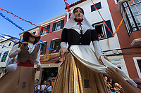 "Spain. Balearic Islands. Minorca (Menorca). Mahon. The parade of the Giants in the ""Festes de la Mare de Déu de Gràcia"" during the traditional summer festival. Maó (in Catalan) and Mahón (in Spanish), written in English as Mahon, is a municipality, the capital city of the island of Menorca, and seat of the Island Council of Menorca. The city is located on the eastern coast of the island, which is part of the autonomous community of the Balearic. In Spain, an autonomous community is a first-level political and administrative division, created in accordance with the Spanish constitution of 1978, with the aim of guaranteeing limited autonomy of the nationalities and regions that make up Spain. A flag of Menorca is fixed on the wall in between two windows. The flag of Menorca was adopted on 14 November 1983. It is based on and is the predominantly red and yellow Catalan-Aragonese (Senyera) flag with the coat-of-arms of Menorca. 7.09.2019 © 2019 Didier Ruef"