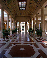 View down a colonnaded hallway with a coloured glass skylight and a trompe l'oeil coffered ceiling