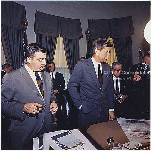 Signing of Commission for General Dwight D. Eisenhower in the Oval Office at the White House on March 24, 1961.  Left to right: Press Secretary Perre Salinger;  United States Secretary of Defense Robert S. McNamara;  U.S.  President John F. Kennedy,  photographers. .Credit: White House via CNP
