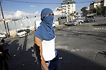 A masked Palestinian youth looks on during clashes with Israeli security forces after Moataz Higazi was shot in east Jerusalem October 30, 2014. Israeli police shot and killed Higazi suspected of trying to kill a hard-line Jewish activist in Jerusalem, an incident that quickly sparked clashes between masked stone throwers and Israeli riot police, threatening to further enflame the already high tensions in the city. Photo by Muammar Awad