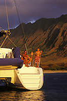 Father and son relaxing on sailboat off Makua Beach, West Side Oahu