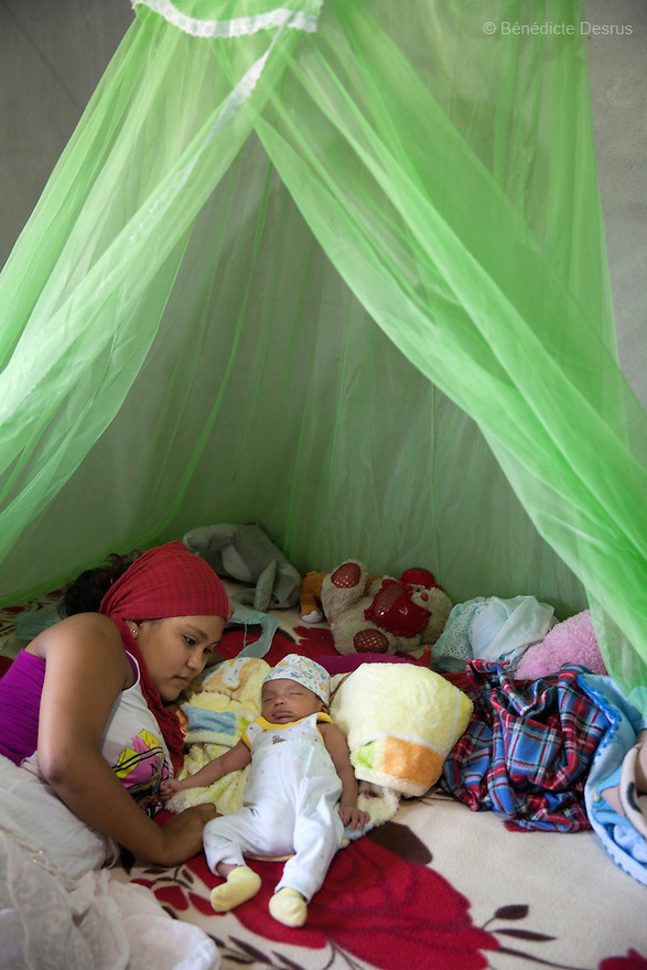 "Luz Betsaida Orozco Pineda and her new born baby at their home in Juchitán, Mexico on February 17, 2016. Now 14, Luz became pregnant when she was 13 after being ""stolen"" according to the Zapotec Indigenous tradition. Considered a traditional kind of marriage – Luz is too young to wed legally – the custom dictates that the couple go to the young man's house and announce their plans to marry. While the family waits, the couple go to a room together; he emerges later with a blood-stained handkerchief to prove his bride's virginity. Luz, who started going out with the father of her baby when she was 10, lives with her in-laws in the 6 de noviembre neighbourhood on the outskirts of Juchitán in the southern Mexican state of Oaxaca. Her baby was born on January 13, 2016. Despite following tradition, she speaks little Zapotec – the language of her husband and his family – she follows tradition, wearing a headscarf to protect her health as she is still observing the 40-days quarantine period after giving birth, during which she stays in the house. While Mexico has outlawed marriage under the age of 18, many young girls become unofficial wives and mothers much earlier. In Juchitán, teenage pregnancy is expected, even prized. Mexico ranks first in teenage pregnancies among the member countries of the Organization for Economic Co-operation and Development (OECD). Photo by Bénédicte Desrus"