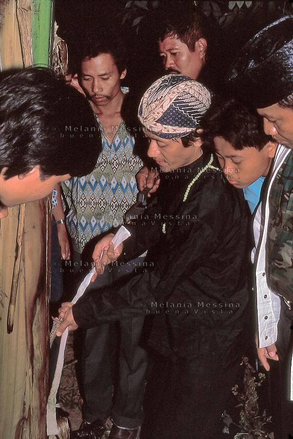 Indonesia, Java island; Pak Iman discovering the kris after the ritual..Indonesia, isola di Giava; l dukùn Pak Iman trova il kris dopo il rituale.
