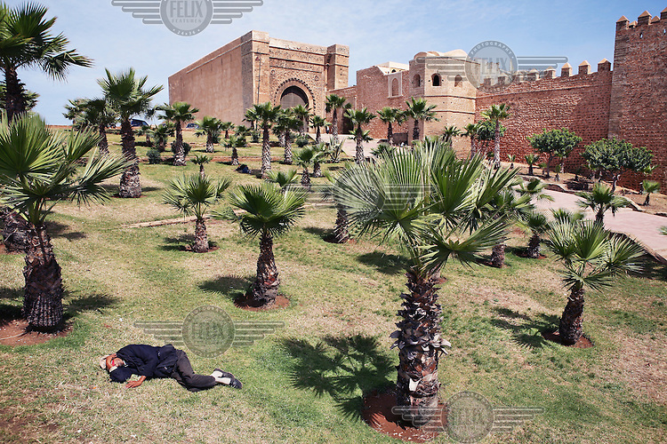 Man sleeping in a park in front of the Oudaia Kasbah in Rabat. The kasbah got its name from the Arabic Oudaia tribe who was asked by the Sultan Moulay Ismail to defend the city of Rabat.