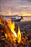 INDONESIA, Flores, Riung, view of a man enjoying the sunset, taken through a beach bonfire, Rutong island