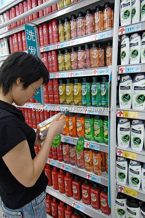 A customer looks at a rack of shampoo products in a supermarket in Chengdu, China. A rapidly expanding middle class has created a large market for many products not previously sold in China..20 Sep 2006