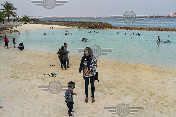Families relax on an artificial beach.
