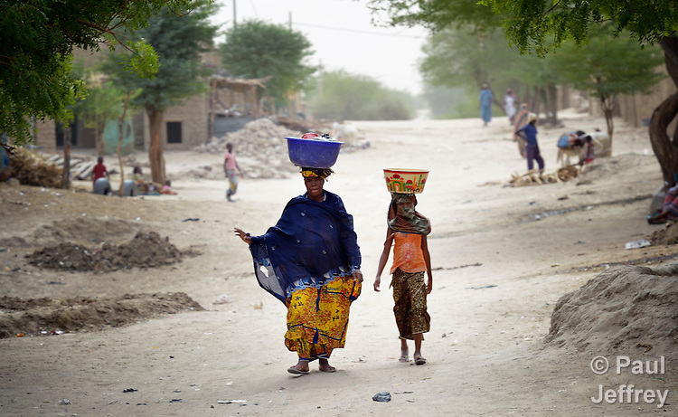 A woman and girl walk along a street in Timbuktu, a city in northern Mali which was seized by Islamist fighters in 2012 and then liberated by French and Malian soldiers in early 2013.