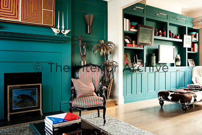 In the living room, the painted wooden panelling and bookshelves were inspired by the Georgian period and painted in a teal colour by the Paint and Paper Library. The extended cabinetry conveniently compensates the lack of existing storage space in the house. The beautifully eccentric brass palm lights are by Maison Jansen.