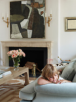 A young member of the family is seen in the living room where the custom sofa is covered in a Donghia mohair. A painting by Santiago Castillo hangs above an 18th-century French limestone fireplace, the stools are by Maison Jansen, the crystal chandelier is 19th-century and the abaca rug is by Patterson Flynn Martin.