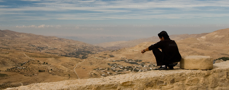 High Perch.  A young man perches right on the edge of Karak Castle's battlements, atop a sheer face several hundred feet above the Wadi al-Karak, below.  The bluffs on the Israeli side of the Dead Sea are clearly visible in the distance.  According to legend, the ancient Biblical condemned cities of Sodom and Gomorrah were between Karak and the Dead Sea, in this view.  The Crusader castle at Karak guarded the eastern border of the Kingdom of Jerusalem after the first Crusade. © Rick Collier