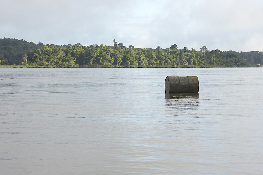 Discarded fuel barrel floating down the Marowijne River, Suriname.