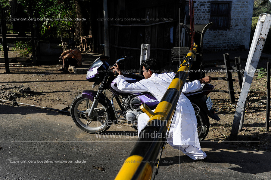 INDIA, Madhya Pradesh, Nimad region, Khargone, motorbike driver violate traffic rules while crossing a Railroad Crossing with closed barriers