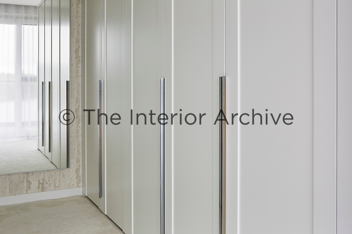 The elegant, bespoke wardrobes provide plenty of storage space in the dressing room.