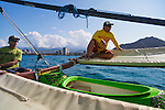 Riding a double-outrigger, single hull sailing canoe off of the east end of Waikiki beach, launching from Outrigger Club Beach.  George Kam, the ambassador of Aloha for Quicksilver, is in the center of the boat, the captain is Dale Hope and the paddler in front is George's brother, Kent Kam.