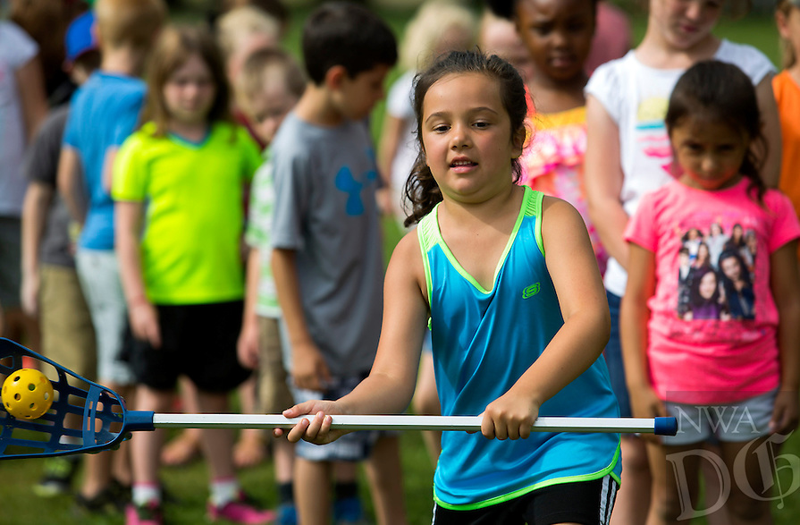 NWA Democrat-Gazette/JASON IVESTER<br /> Jenna Mondragon (cq), 6, tries her hand at lacrosse on Monday, June 13, 2016, outside the Rogers Activity Center. Jenna and others are participating in the center's summer day camp.