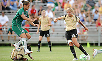 Nikki Cross (green) jumps over Formiga as Carrie Drew attempts a pass..Saint Louis Athletica tied 1-1 with F.C Gold Pride, at Anheuser-Busch Soccer Park, Fenton, Missouri.