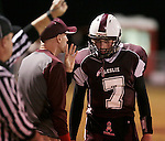 Coach Russell Melton gives quarterback Kevin Whitaker the next play during Leslie County's game against Betsy Layne at Leslie County High School in Hyden, Ky. on Friday, October 11, 2013. Photo by Adam Pennavaria