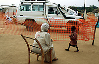 Sudan. West Darfur. Kerenek. The non-governmental organization (ngo) Médecins sans Frontières (MSF) Switzerland runs a medical program and a clinic. A child walks near a MSF watchman seated on a wood chair. The Toyota Landcruiser used as an ambulance is parked outside the orange plastic fence. © 2004 Didier Ruef