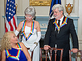 Singer-songwriter Carole King, left, actress and singer Rita Moreno, center, and filmmaker George Lucas, three of the five recipients of the 38th Annual Kennedy Center Honors share a conversation prior to posing for a group photo following a dinner hosted by United States Secretary of State John F. Kerry in their honor at the U.S. Department of State in Washington, D.C. on Saturday, December 5, 2015.  The 2015 honorees are: singer-songwriter Carole King, filmmaker George Lucas, actress and singer Rita Moreno, conductor Seiji Ozawa, and actress and Broadway star Cicely Tyson.<br /> Credit: Ron Sachs / Pool via CNP