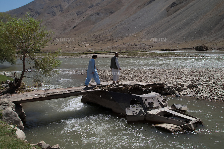 """AFGHANISTAN - VALLEE DU PANJSHIR - 18 aout 2009 : Riviere du Panjshir. Carcasse de char pris aux russes par les Moudjahidin du Commandant Massoud lors de leurs assauts pendant la guerre d'Afghanistan de 1979 - 1989. Dawoud Baraushah, l'ancien garde du corps de Massoud et guide de Reza et Delazad Deghati pendant leur voyage et Delazad franchissent le pont pose sur le char. .La photographie appartient a la serie """"Il etait une fois l'Empire Russe"""". ..AFGHANISTAN - PANJSHIR VALLEY - August 18th, 2009 : Panjshir River. Remnants of a Russian tank seized by Commander Massoud's mujahideen during the Afghan war of 1979-1989 being used to hold up a bridge over the river. Delazad Deghati and Dawoud Baraushah, Commander Massoud's former bodyguard and Reza and Delazad's guide in Afghanistan, crossing the bridge..The photograph is part of the series """"Once Upon a Time, the Russian Empire."""""""