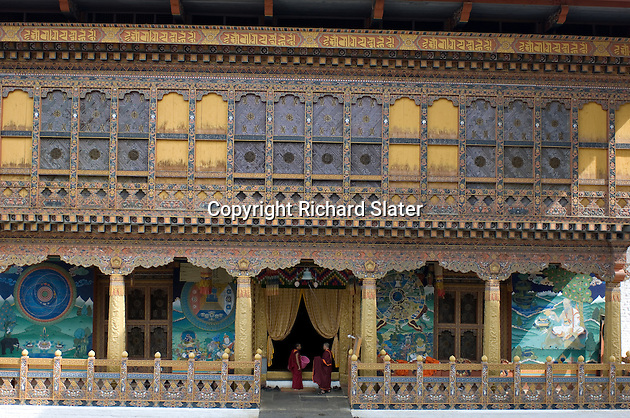 Two monks converse at the entrance to one of the halls off the main courtyard of the magnificent Punakha Dzong in Bhutan, with its wonderfully carved and painted walls and galleries. This dzong, or fortress, now serving as a thriving monastery, was built in AD1637.