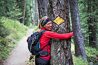A woman stands hugging a tree that has a painted trail marker on it, Switzerland