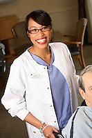 Smiling Ethnic Nurse Helping Elderly Patient