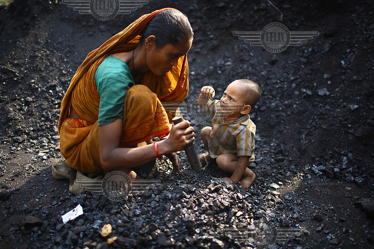 A small boy seeks the attention of his mothers lap as she breaks coal used to fire brick kilns at a factory in Gazipur.