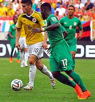 BRASILIA - BRASIL -19-06-2014. James Rodriguez (#10) jugador de Colombia (COL) disputa el balón con Sylvain Gbohouo (#17) jugador de  Costa de Marfil (CIV) durante partido del Grupo C de la Copa Mundial de la FIFA Brasil 2014 jugado en el estadio Mané Garricha de Brasilia./ James Rodriguez (#10) player of Colombia (COL) fights the ball with Sylvain Gbohouo (#17)  player of Ivory Coast (CIV) during the macth of the Group C of the 2014 FIFA World Cup Brazil played at Mane Garricha stadium in Brasilia. Photo: VizzorImage / Alfredo Gutiérrez / Contribuidor