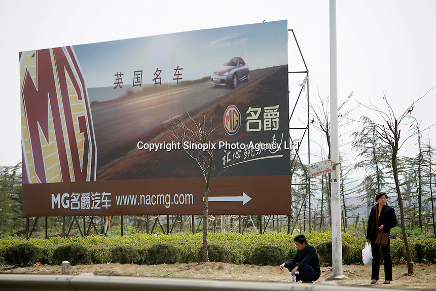 Two chinese waiting for a bus stands near a MG ad in Nanjing, China. The Chinese company is now in a position to take on Rover's assets and plan its future. It intended to relocate the engine plant and some car production plant to China but to retain some car production plant in the UK..27 Mar 2007