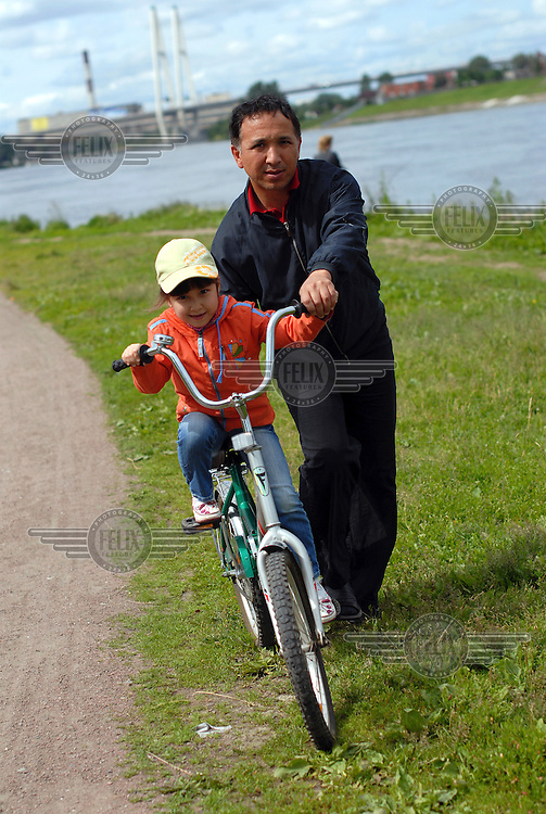 A man teaches his young daughter how to ride a bicycle alongside the Neva river on the fringes of St Petersburg.