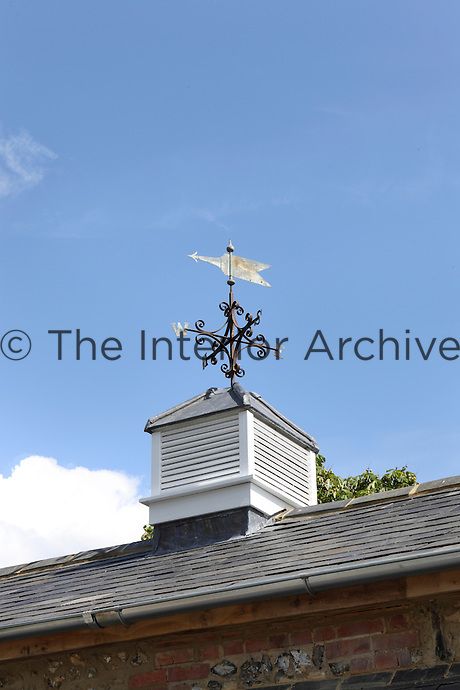 Detail of the slate roof and tower topped with a copper weathervane