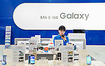 Samsung, Apr 29, 2015 : A woman uses a Samsung mobile phone at Galaxy Zone, a store for display and sale of Samsung Electronics products in Seoul, South Korea. Samsung said on Wednesday its net profit plunged 39 percent in the first quarter from a year earlier because of weak earnings from mobile business, local media reported. (Photo by Lee Jae-Won/AFLO) (SOUTH KOREA)