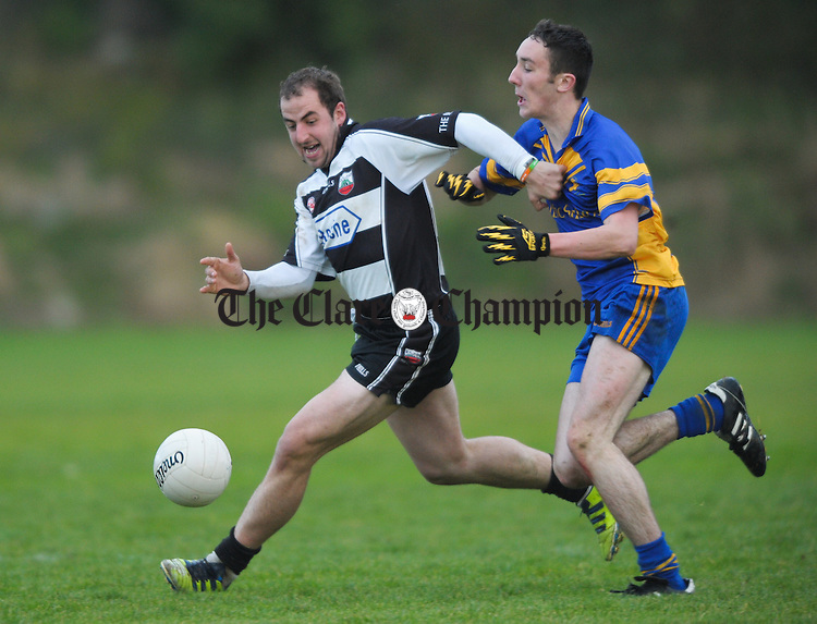 Adam Healy of Clarecastle in action against Ronan Rafferty of Michael Cusack's during their Junior A football final at Corofin. Photograph by John Kelly.