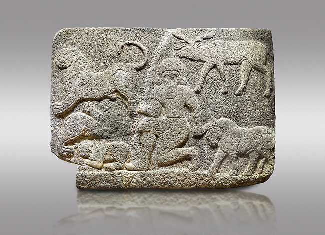 Hittite relief sculpted orthostat stone panel of Herald's Wall Basalt, Karkamıs, (Kargamıs), Carchemish (Karkemish), 900700 B.C. Anatolian Civilisations Museum, Ankara, Turkey.<br /> <br /> In the middle is a kneeling bearded figure holding the bull's horn with his left hand and the lion's hind leg with his right hand. Below this lion is another lion whose chest and the head are missing, and below this second lion is another small lion. A deer stands behind his head. It is thought that this relief depicts Gilgamesh, the master of animals.