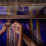 Two women operate a traditional loom to weave cloth in Kalay, a town in Myanmar.