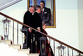 United States President Bill Clinton, center, Chancellor Helmut Kohl of Germany, left, and first lady Hillary Rodham Clinton, right, descend the Grand Staircase of the White House in Washington, DC prior to posing for a photo prior to an Official Dinner in the Chancellor's honor on Thursday, February 9, 1995.  The portrait in the background is the official portrait of former US President Ronald Reagan.<br /> Credit: John Harrington / Pool via CNP