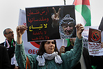 Palestinian protesters hold placards as the convoy of Jerusalem's Greek Orthodox patriarch Theophilos III arrives in the West Bank town of Bethlehem on January 6, 2018 ahead of a Christmas service according to the Eastern Orthodox calendar. The municipalities of Bethlehem, Beit Sahour and Beit Jala, all in the Israeli-occupied West Bank, called for the boycott over Jerusalem's Greek Orthodox patriarch allegedly allowing controversial real estate sales. Photo by Wisam Hashlamoun