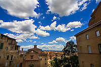 Clouds pass over the Terra Cotta roofs of Siena, Italy.