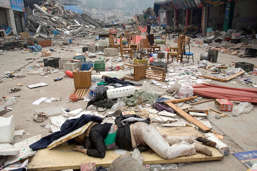 A body lies in the rubble of a destroyed market in Beichuan Town, which was severely damaged by a powerful 7.9 earthquake. The Chinese government raised the death toll to 21,500 but has said fatalities could rise above 50,000. Tens of thousands could still be buried in collapsed buildings in Sichuan province, where the quake was centered.