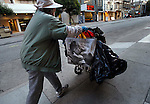 A woman strolls her shopping cart down the sidewalk of San Francisco Tenderloin district.