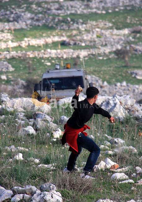 Palestinian protestors hurl stones at Israeli troops in the West Bank village of Iraq Borin near Nablus, on 05 March 2011. Two Palestinians were wounded after Israeli troops raided the village to stop clashes between Palestinians and Israeli settlers. Photo by Wagdi Eshtayah
