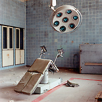 An chair lies overturned in the operating theatre of a deserted hospital of the Soviet Army.  The Cold War, which formed part of the collective consciousness of post war Europe from 1945 until 1989 dominated the military and political landscape.  Often highly charged with nationalistic zeal, Soviet rhetoric and paranoia, relics of the Cold War remain as testaments to the covert era within Eastern Europe. CHECK with MRM/FNA