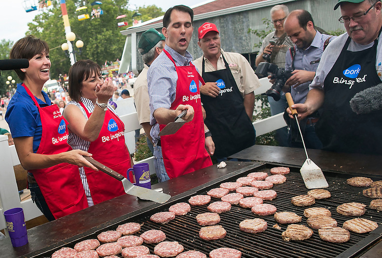 UNITED STATES - August 17: Governor of Wisconsin and Republican presidential candidate Scott Walker, shows off a new way to flip meat as he stands beside his wife, Tonette, center, and Iowa Lieutenant Governor Kim Reynolds, at the Iowa Pork Producers Association site at the Iowa State Fair in Des Moines, Iowa, Monday, August 17, 2015. (Photo By Al Drago/CQ Roll Call)