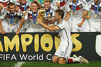 Thomas Muller of Germany lifts the World Cup trophy after winning the 2014 final with his team mates Bastian Schweinsteiger , Andre Schurrle and Philipp Lahm