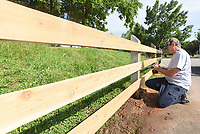NWA Democrat-Gazette/FLIP PUTTHOFF <br /> MENDING FENCES<br /> Carl Pullum with Rogers Parks and Recreation Department repairs a fence Tuesday June 4 2019 at Veterans Park in Rogers. A vehicle hit the fence and damaged it, Pullum said.