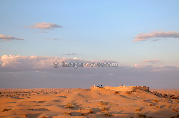 Africa, Tunisia, Ksar Rhilane. Tourists enjoying the sunset at the remains of the old historic roman fortress Ksar Ghilane three kilometers to the north east of the oasis Ksar Ghilane.